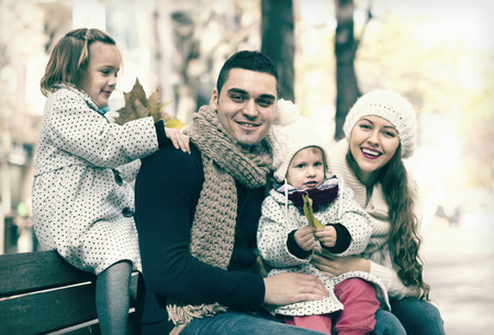 portrait of happy parents with two daughters in autumn park. Focus on man photo