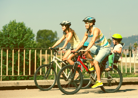 Young family of four people with bikes in sports helmets outdoors photo