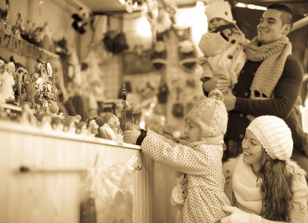 Happy married couple at Catalan Christmas market. little girl touch toys photo