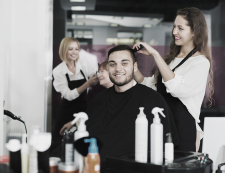 Positive professional adult woman hairdresser doing hairstyle for young men photo