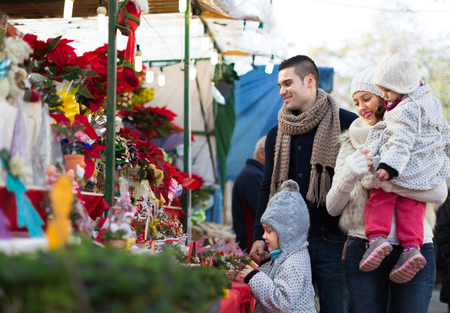Happy young parents with little girls at counter with Poinsettia. Shallow focus photo