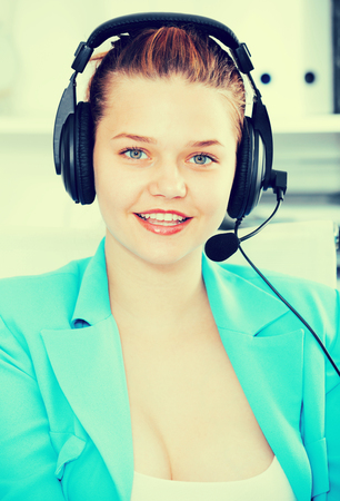dispatcher: Office worker woman is working at a computer and talking by headset with client in the office.