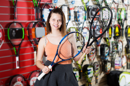 Smiling young woman holding in hand racket for badminton in sport shop Stock Photo