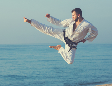 young man practicing karate positions at ocean quay