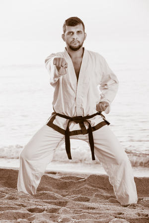 Young man doing karate at ocean quay in dawn