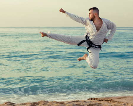 Serious positive  young man in uniform doing taekwondo exercises at  sunset sea shore