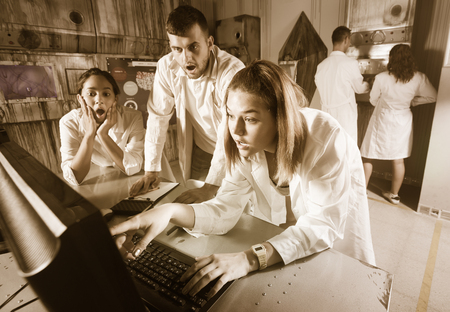 Company of young people solving different conundrum in quest room in view as abandoned lab