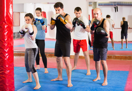 Portrait of young cheerful positive females and adult males training in boxing gloves