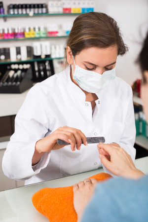 Manicurist filing and shaping nails during procedure of manicure in beauty salon