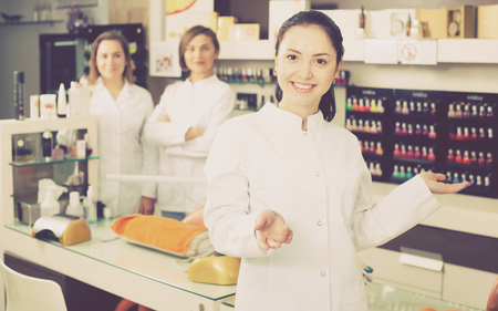 Smiling woman nail technician welcoming to modern beauty salon