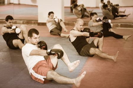 Portrait of  positive females and adult males training in boxing gloves Stock Photo