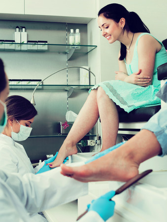 Nail pedicure master performing procedure for foot care in nail salon