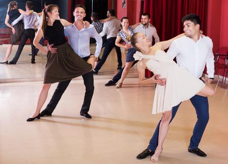 Happy adult dancing couples enjoying latin dances in modern studio Stock Photo