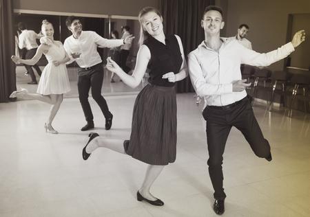 Adult dancing couples enjoying active dance in modern studio Stock Photo
