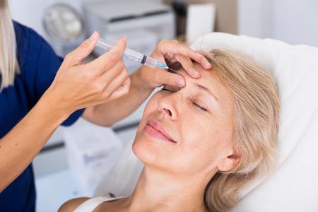 Cliente femminile maturo che riceve iniezione cosmetica dall'estetista professionista Archivio Fotografico - 84248918