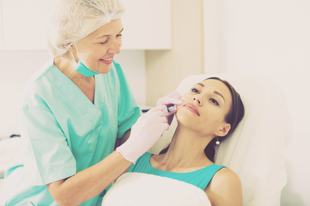 esthetics: Female client receiving cosmetic injection from professional cosmetician Stock Photo