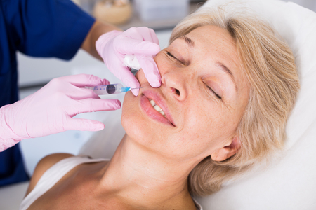 Mature female client receiving cosmetic injection from professional cosmetician Stock Photo