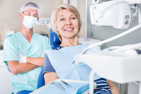 歯医者で歯の治療後の笑顔の女性患者が満足 写真素材