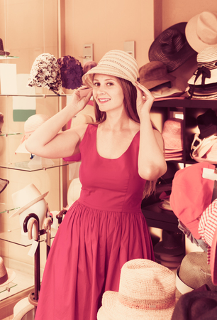 adult positive woman try on hatinator hat  in shopping mall