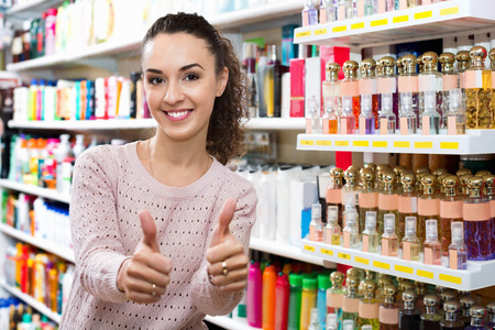 supermarket: Young female customer posing near shelves with cosmetic products Stock Photo