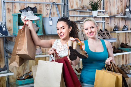 Two  beautiful happy young girls holding a paper shopping bags in the boutique