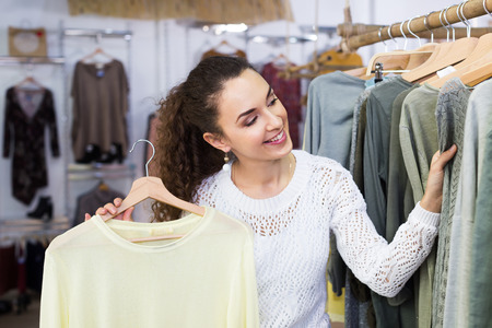 Excited woman buying pullover at the apparel store
