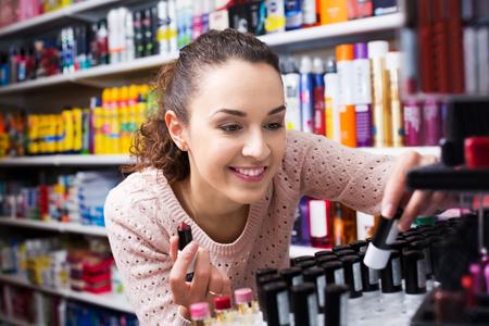 lustre: Portrait of positive young brunette selecting lipstick at beauty shop