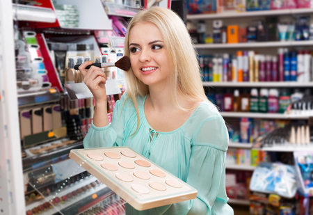 Portrait of happy girl selecting face powder at beauty store