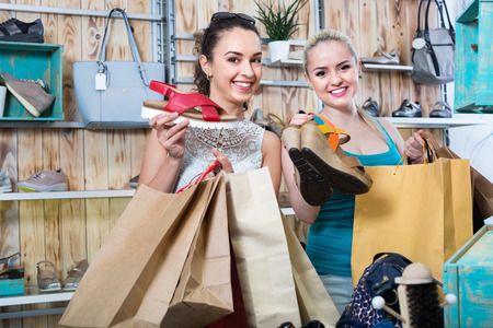 Two  happy young girls holding a paper shopping bags in the boutique