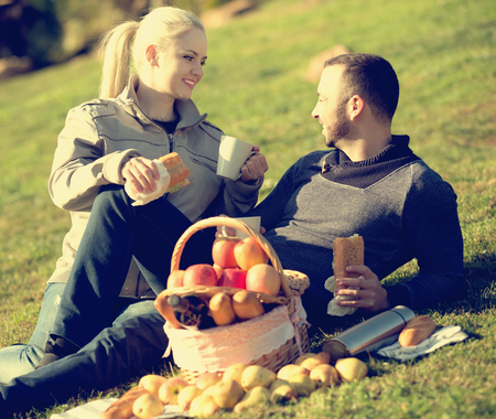 Young smiling family couple lounging in sunny spring day at picnic outdoors. Focus on girl
