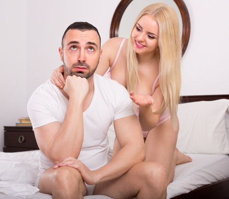 remit: Attractive young blonde making efforts to reconcile with displeased boyfriend in bed. Focus on guy Stock Photo
