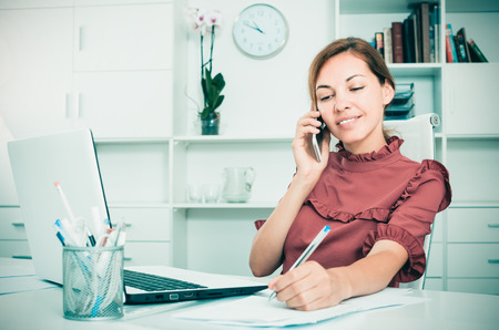 young attentive female employee answering on phone and taking notes at office Stock Photo