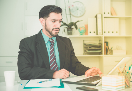 expertize: Adult businessman is sad because he is having issues at work place in office.