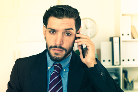 expertize: Adult man is serious talking phone in his work place.