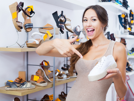Smiling young woman holding desired shoe in hands in fashion boutique Stock Photo