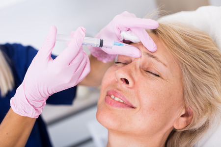 esthetics: Portrait of woman during beauty facial injections in medical esthetic office