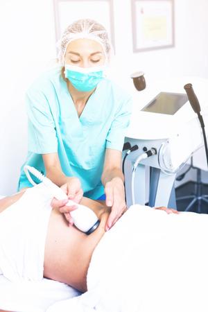 Estetista facendo procedura innovativa di crisiposuzione alla femmina nell'ufficio cosmetico Archivio Fotografico - 84618594