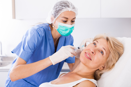 esthetics: Senior woman getting injection for facial rejuvenation procedure in esthetic clinic