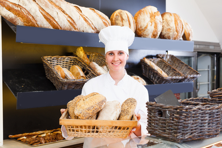 Female is offering fresh baguettes and buns in bakery.