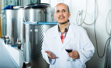 Winery worker wearing coat holding glass of wine in fermenting section