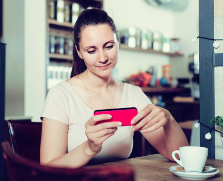 Young cheerful european woman using mobile phone in cafe