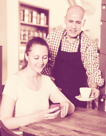 Young waiter brought coffee to a girl which is surfing in phone. Stock Photo