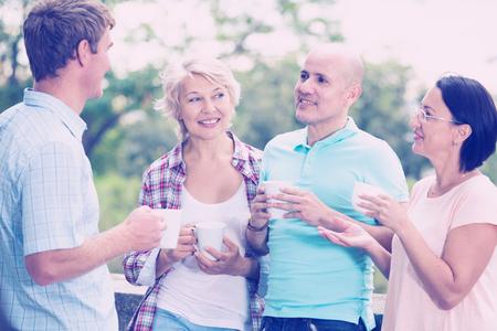 성숙한 명랑 남성과 여성 야외 커피를 마시는
