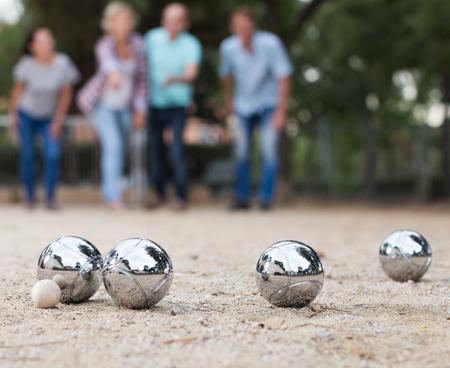 Mâles et femelles jouant à la pétanque dans le parc en vacances Banque d'images - 84321016