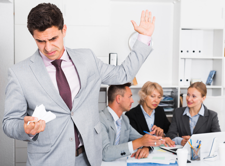 Irritated businessman standing in modern office on background of working associates