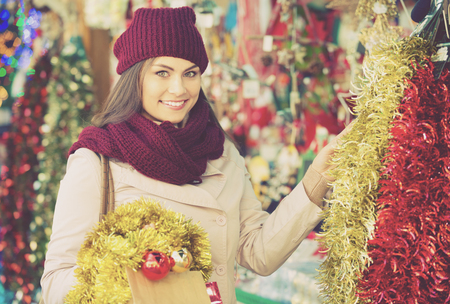 overspending: Portrait of female customer near counter with Christmas decoration