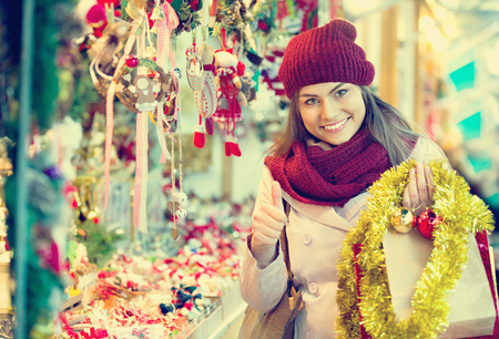 Beautiful happy smiling woman choosing Christmas decoration at market