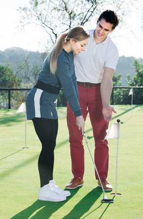 Man 30-35 years old is training woman 25-29 years old to play golf and hit ball correctly. Stock Photo