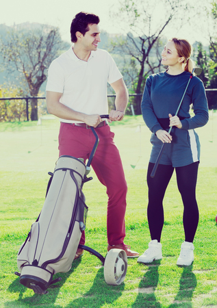 brassy: Smiling male and female golf players are ready for tour of game at golf course