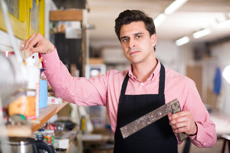 Portrait of craftsman with tool in hand near shelves in carpentry